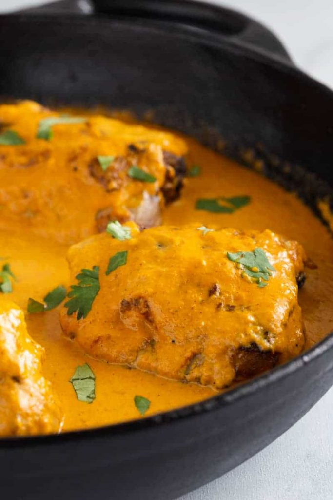 side view of butter chicken sauce in a pan with chicken